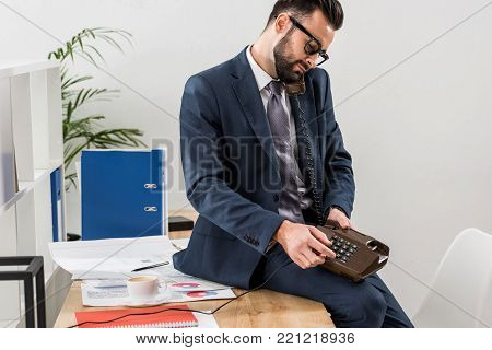 businessman talking by stationary telephone in office and sitting on table
