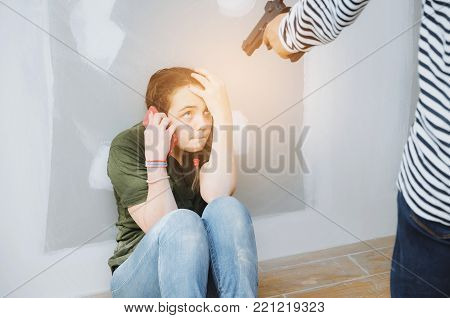 thief in black and white jacket with gun and caucasian girl calling with phone, fearing and sitting on floor in abandoned house background, hostage, dangerous criminal, illegal violence concept