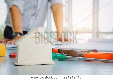 wooden house model and tools on conference table with architect, engineer planning start up new project in background at construction site, successful, industry, architecture, housing project concept