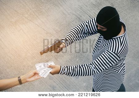 thief or robber in black and white jacket and masked hood with gun threatens man or woman fo steal money, dangerous criminal in the city, victim, violence, crime and steal concept