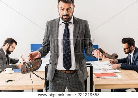 businessman standing with stationary telephone in office