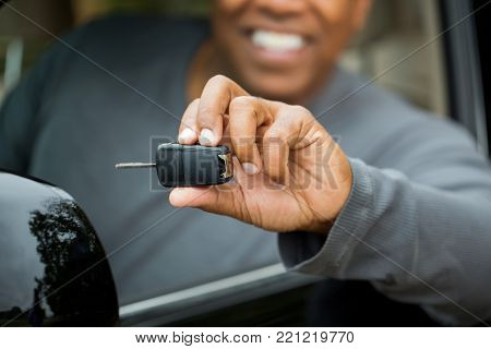 African American man holding the keys to his new car.