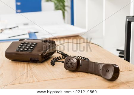handset of black stationary telephone on table