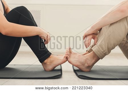 Young couple practicing yoga together. Unrecognizable man and woman close and touching feet, copy space