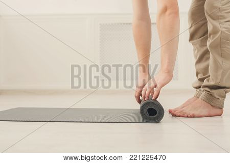 Pilates background. Unrecognizable man rolling up yoga mat after training. Sport class before or after practicing yoga, preparing for exercise, side view, copy space