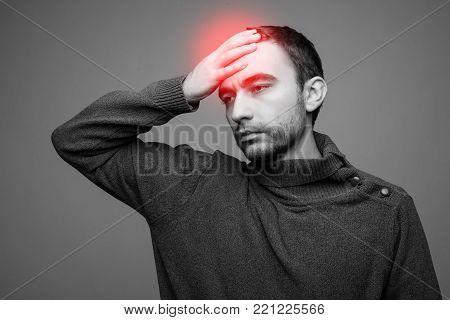 A Young Man Grasping His Head Where The Pain Is - A Killer Headache Or Migraine.