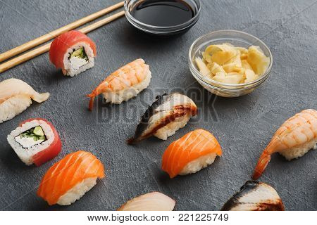 Sushi, rolls, soy sauce and ginger on gray background. Colorful japanese restaurant food set with chopsticks for one person. Asian meals take away and delivery, closeup