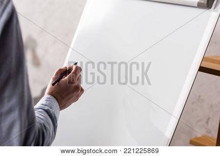 cropped image of businessman writing something on flipchart