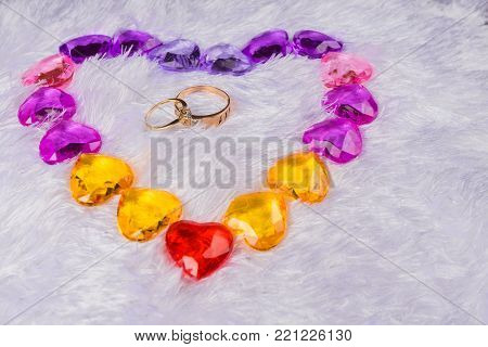 Heart lined with small glass hearts lying on a bed of faux fur in the center of it are two wedding rings