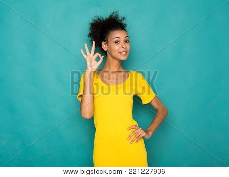 Young beautiful african-american woman showing ok sign. Cheerful girl gesturing that all is great, blue studio background