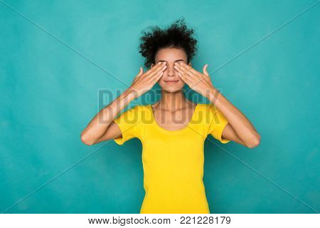 See no evil concept. Portrait of young african-american woman covering eyes with hands while standing against blue studio background. Confused girl close eyes with palms ignoring something