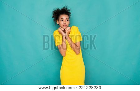 Unpleasant situation. Scared african-american woman feeling fear, afraid to be attacked, blue studio background