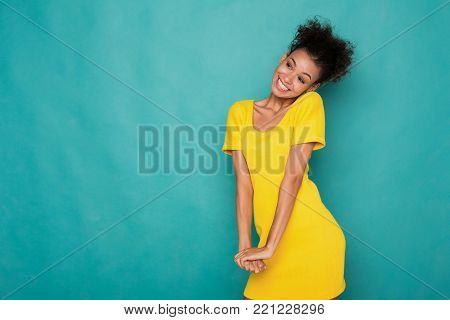 Beautiful african-american woman shy and confused, smiling and posing on blue studio background, copy space