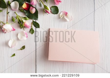 Valentine background with pink rose flowers petals and handmade paper card, top view on white rustic wood. Happy lovers day mockup, copy space.