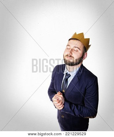 The concept of leadership, excellence. Portrait of a smiling man with a golden crown on his head.