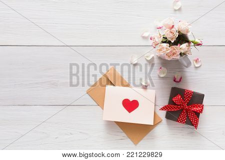 Romantic background pink rose flowers bouquet petals, present box, handmade greeting card with hearts on white rustic wood. Happy lovers day mockup, romantic, top view, copy space