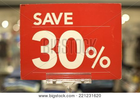 Save thirty percent red sign board against a store background