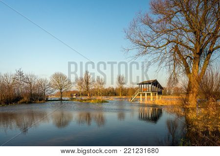 Birdwatching hut in a flooded Dutch nature reserve  situated on a wide river. The river has overflowed the banks due to the high water level due to the large amount of water coming from Germany.