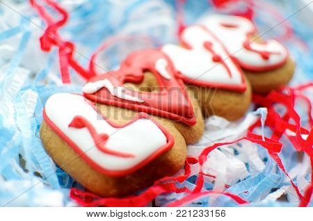 Letter cookies for Valentine's day or for a wedding day on the blue and white paper filler background. Top view, selective focus, copy space.