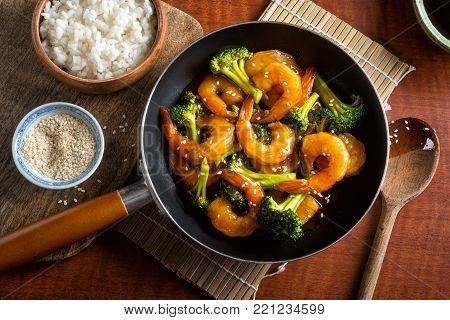 A delicious shrimp teriyaki stir fry with broccoli and sesame seeds on a wooden table top.