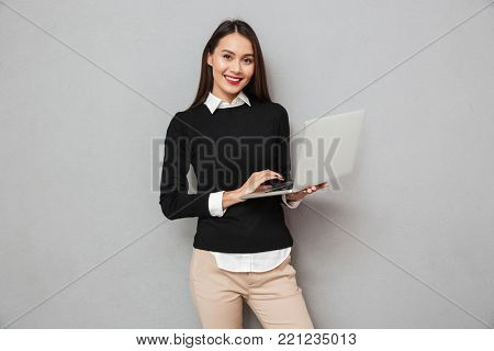 Smiling asian woman in business clothes using laptop computer while looking at the camera over gray background