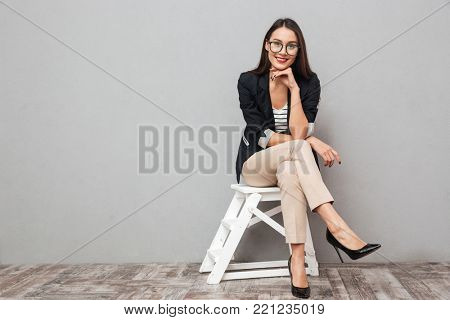 Smiling asian business woman in eyeglasses sitting on chair and looking at the camera over gray background