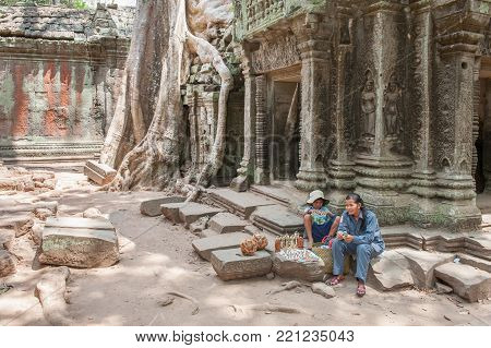 SIEM REAP, CAMBODIA - MARCH 9, 2009: Khmer vendor at Ta Prohm in Siem Reap. Built in 12-13th century Ta Prohm was later the location for the movie Tomb Raider.