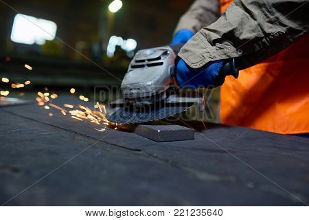 Close-up shot of unrecognizable worker wearing uniform and hand-protection gloves using angle grinder while wrapped up in metalworking at production department of modern plant.