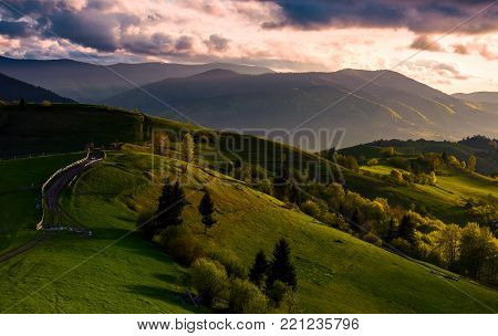 countryside road through grassy rural fields on rolling hills at sunset. spectacular mountainous springtime landscape with gorgeous cloudy sky