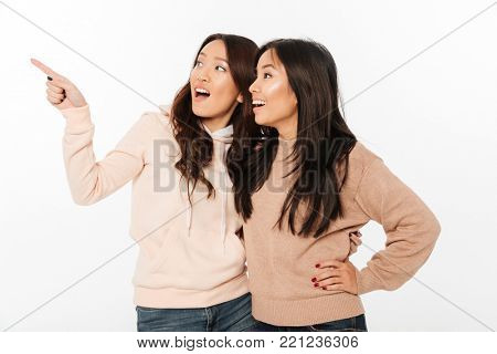 Image of two asian pretty happy ladies sisters hugging with each other. Looking aside pointing.