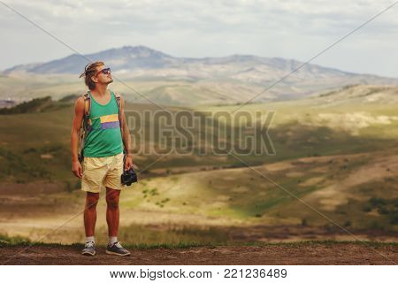A young man with a camera in the mountains of Altai.