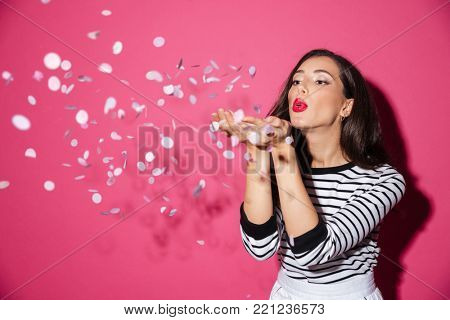 Portrait of a pretty woman blowing confetti from her hands isolated over pink background