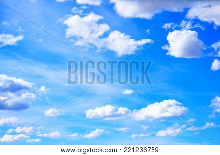 Blue sky background with white clouds in the sly lit by sunlight. Natural sky background, sky sunny landscape. Sunny sky background, blue sky with white dramatic clouds