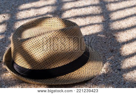A brown straw hat lies on the sand, casts a shadow in the shade of a summer day rest