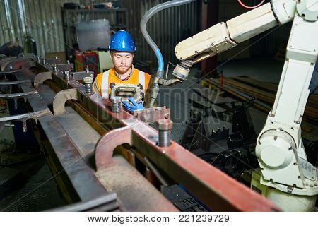 Head and shoulders portrait of bearded red-haired technician wearing reflective vest and hardhat operating machine, interior of production department on background