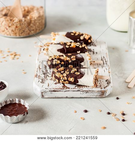 Ice Cream Popsicles Coated with Chocolate and Topped with Granola, square
