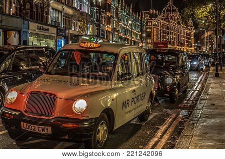 LONDON, ENGLAND - NOVEMBER 29, 2017: Night view with typical London taxis on moving in front of Harrods, the biggest luxury department store from the Europe.