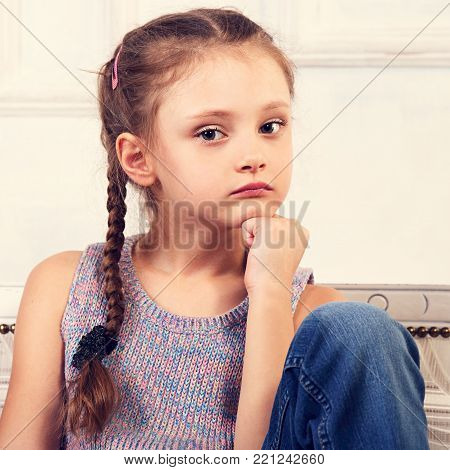 Angry Thinking Kid Girl Sitting On The Bench In Blue Dress And Looking Up. Studio Portrait. Closeup