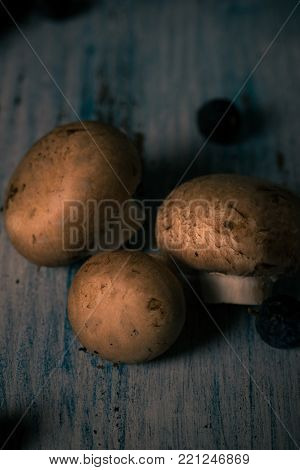 Brown Edible Mushrooms Spilled On Blue Vintage Wooden Board