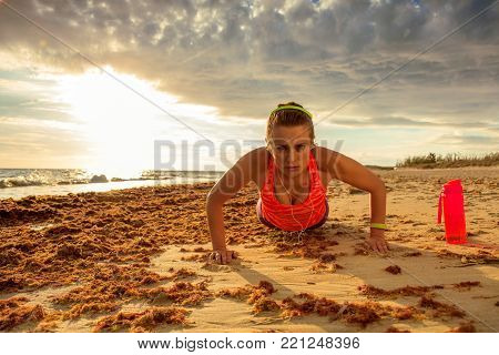 Fitness Woman On Seashore With Headphones Listening To Music