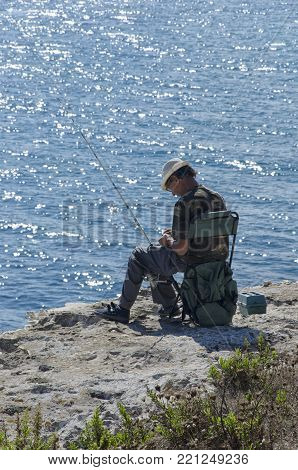 Torre dell'Orso, Italy - September 22, 2017: Solitary fisherman on the Salento cliff