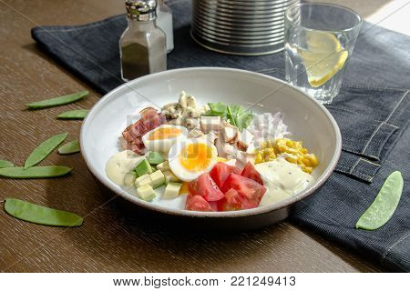 Healthy Hearty Cobb Salad with Chicken, Bacon, Tomato, Onions, Eggs, green beans. American food. Close up, home made cuisine