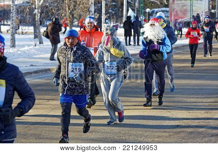 Editorial. Omsk, Russia - January, 07 2018. 27 th Christmas winter half marathon. Athletes of different nationalities and dressed in different costumes running down Partyzanskaya street