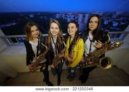 MOSCOW - MAY 18, 2017: Four young women (with model releases) pose with wind instruments on rooftop at night in Elk Island residential complex