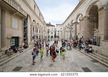 SPLIT, CROATIA - MAY 21, 2017: Tourists visit the courtyard of Diocletians palace with the ancient Roman colonnade in Split