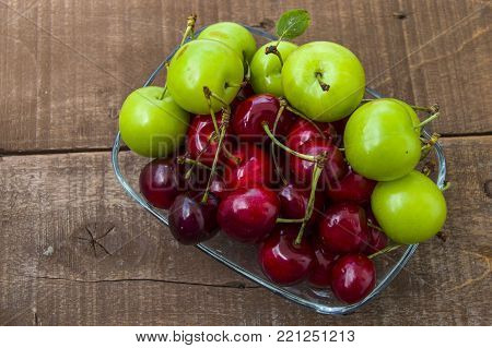 cherry plum and green wonderful summer fruits, delicious sour fruits,  green sour plum, sour summer fruits in a fruit basket, apricot, nectarine, cherry