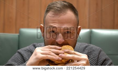 young hipster guy eating burger sitting in cafe.