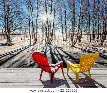 The sun shines low over the horizon. Comfortable red and yellow plastic chaise lounges in forest. Sunset in the Arctic. The concept of extreme and ecotourism tourism