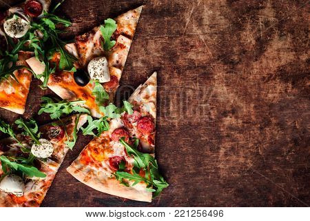 Hot Italian pizza with melted mozzarella cheese and tomato on a rustic wooden table.  Pizza Ready to Eat, Copyspace.