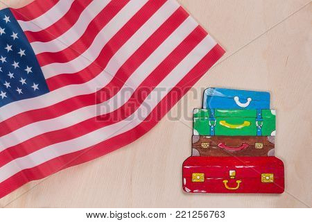 Flag of the United States, word emigration in abstract letters. Wooden background